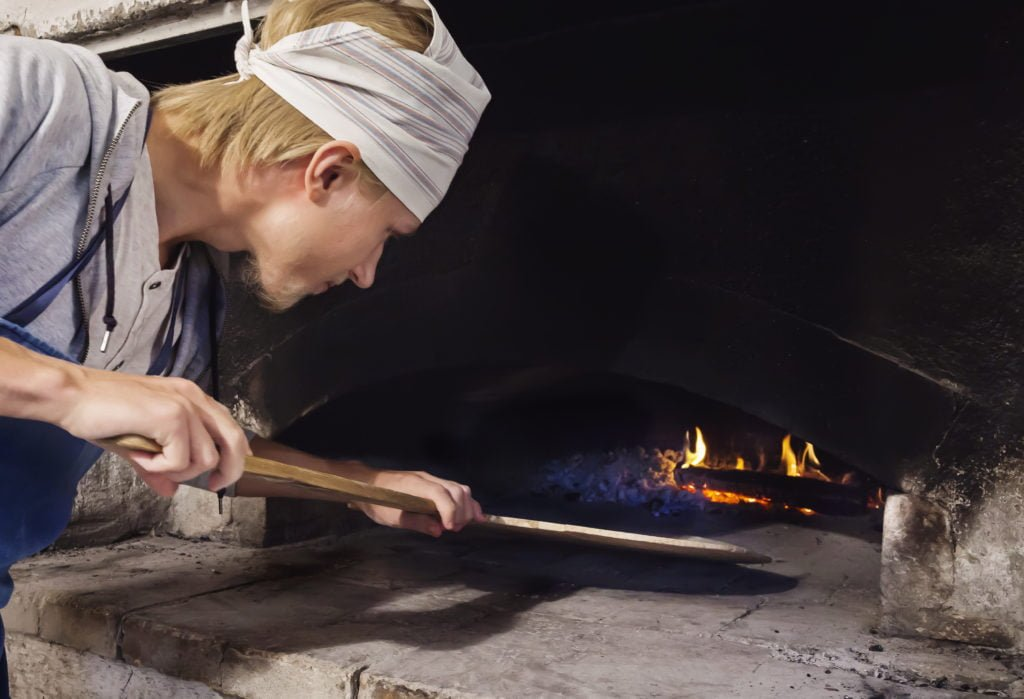 A guest baking bread in a wood-fired oven