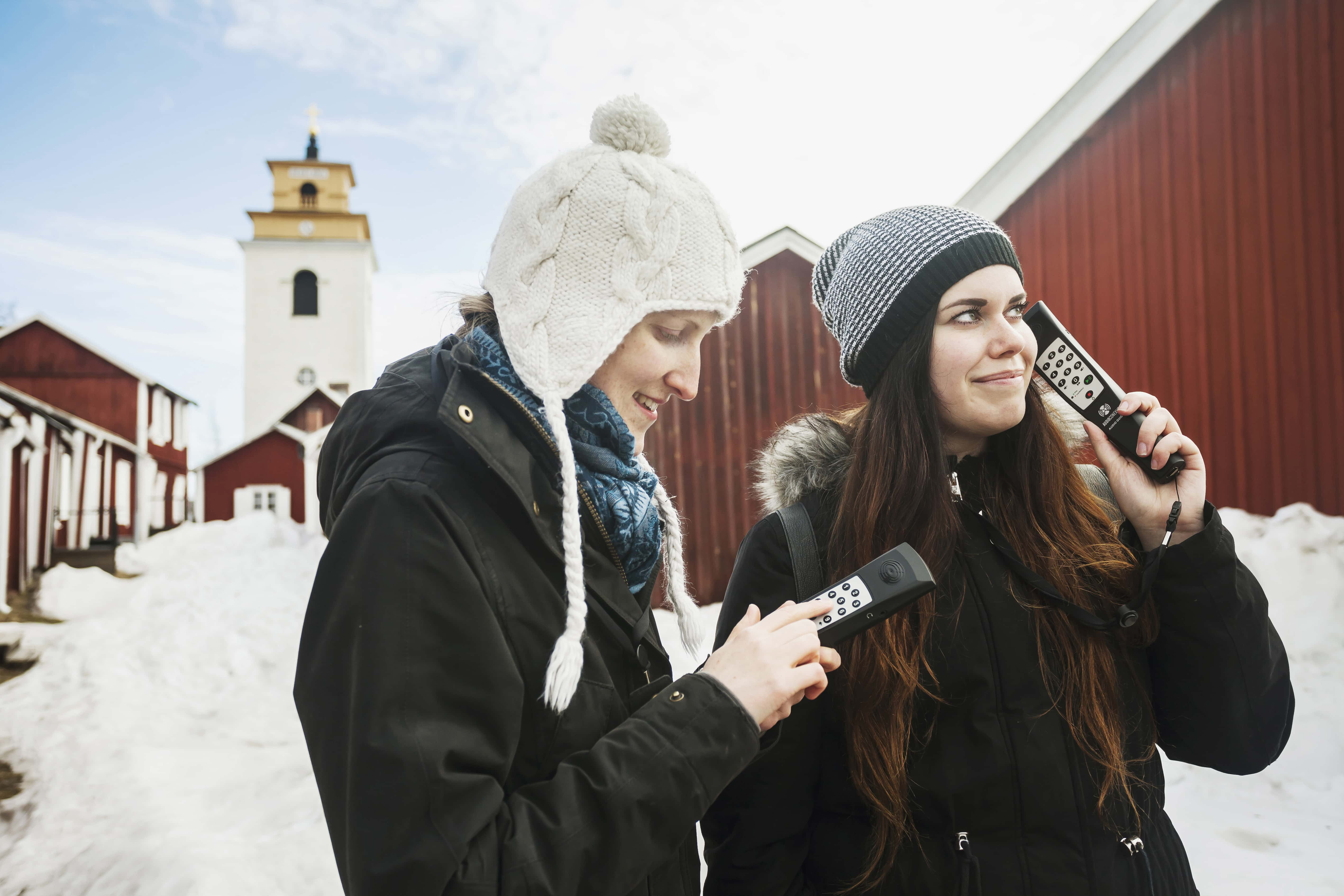 Two visitors listening to an audioguide in Gammelstad Church Town