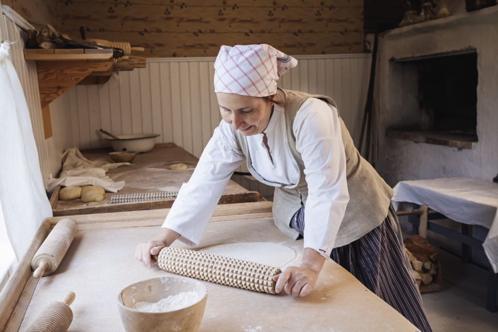 Instructor baking bread in a wood-fired oven